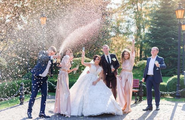 Bruidspaar en beste vrienden drinken champagne en vieren in het park de trouwdag Gratis Foto