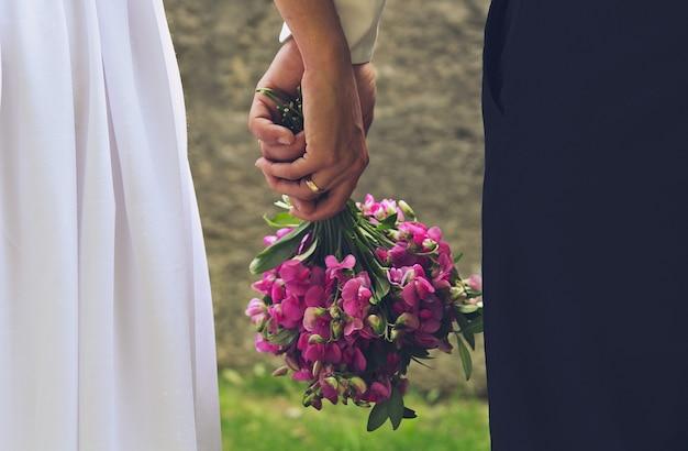 Bruidspaar houdt paars boeket in handen. romantische zomerfoto van verliefde bruid en bruidegom. heldergroene gras en steenmuur. trouwringen en wirwar van armen. Premium Foto