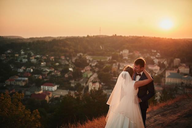 Bruidspaar omarmen bij zonsondergang Premium Foto
