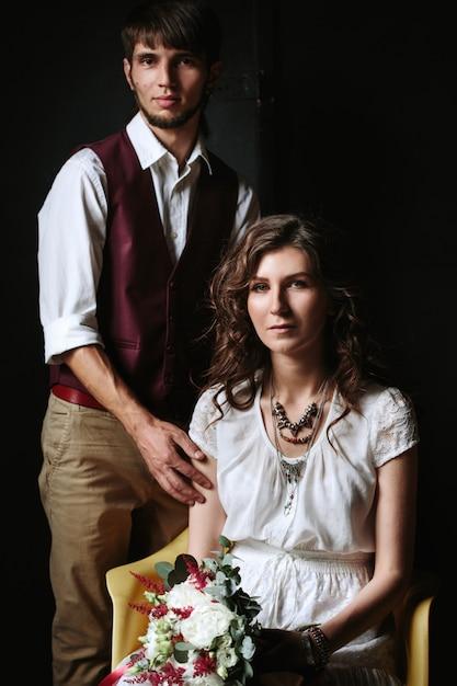 Bruidspaar poseren in het donkere interieur Premium Foto
