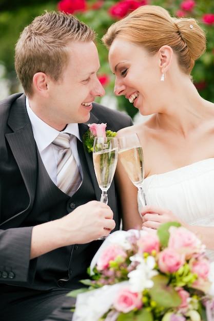 Bruidspaar rammelende champagneglazen Premium Foto