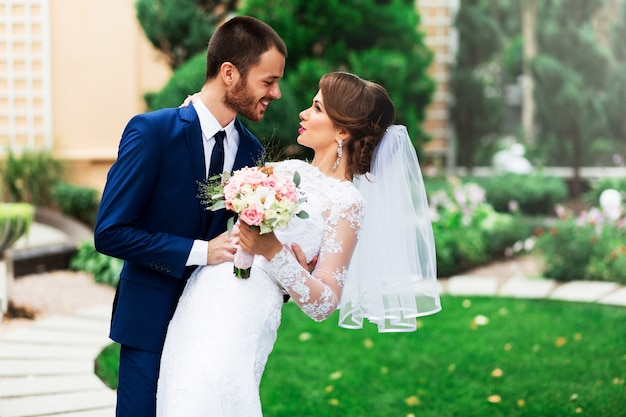 Bruidspaar verliefd kussen en glimlachen. jonge mooie elegante bruid en haar knappe bruidegom poseren in het groene park. Gratis Foto
