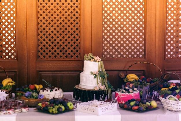 Bruidstaart en snoep staan op blok op het buffet Gratis Foto