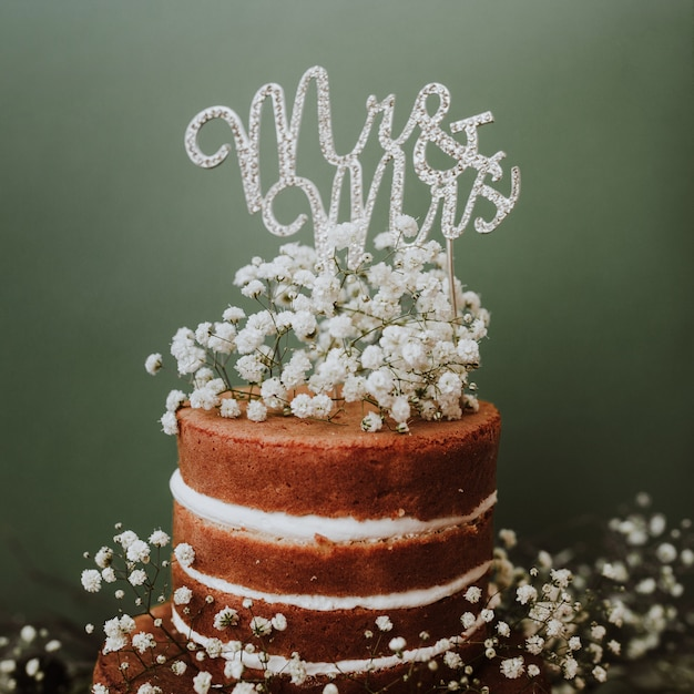 Bruidstaart met paniculata decoratie en de heer en mevrouw topper op groene achtergrond Gratis Foto