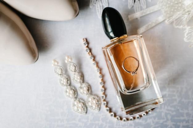 Bruiloft accessoire bruid. stijlvolle schoenen, oorbellen, ketting, gouden ring Premium Foto