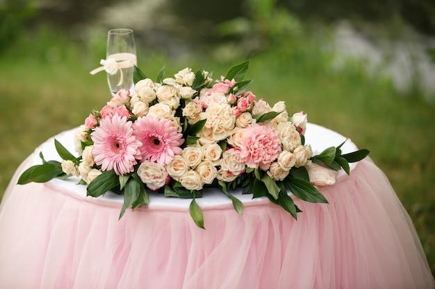 Bruiloft bloemen en champagne glas op tafel Premium Foto