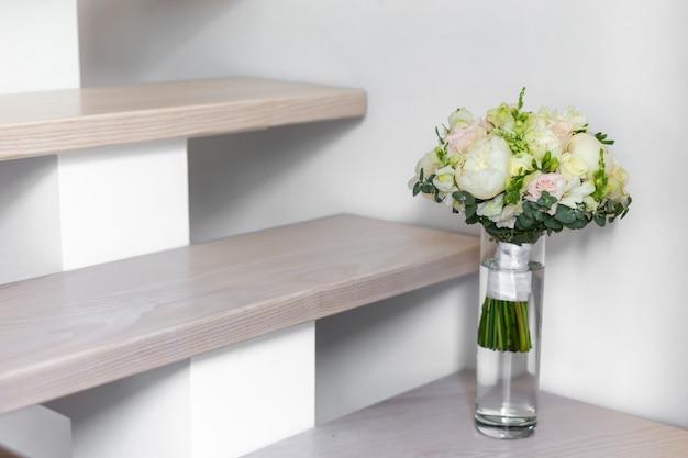 Bruiloft boeket in een glazen vaas op de trap in de buurt van de muur. Premium Foto