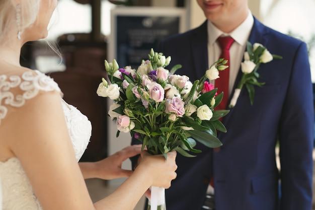 Bruiloft boeket van witte en lila bloemen in de handen van de bruid Premium Foto