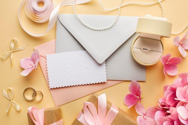 Bruiloft concept bloemen en uitnodiging bovenaanzicht Gratis Foto