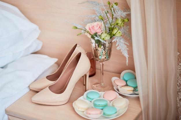 Bruiloft decor. beige bruidsschoenen, boeket en plaat met bitterkoekjes staan op de tafel Gratis Foto