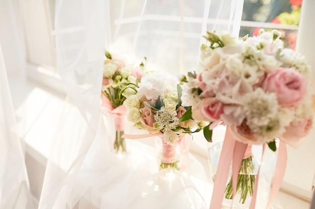 Bruiloft decor. helderroze roos boeket voor een bruid en bruidsmeisjes staan voor een raam Gratis Foto