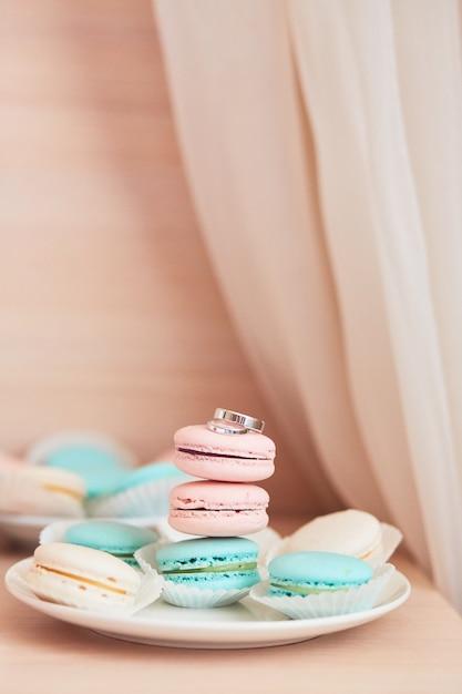 Bruiloft decor. stijlvolle ringen van wit goud liggen op roze en mint bitterkoekjes Gratis Foto