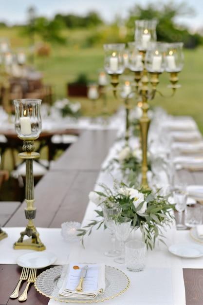 Bruiloft feesttafel ingericht met gasten stoelen buiten in de tuinen met brandende kaarsen Gratis Foto
