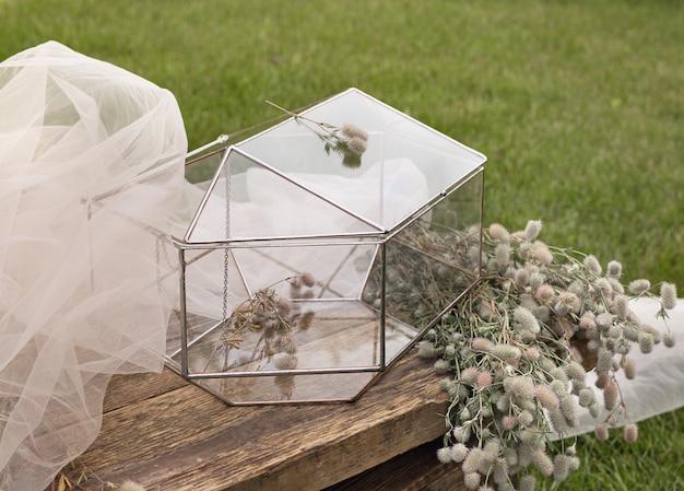 Bruiloft glazen doos voor enveloppen voor groeten op houten tafeltje en het witte weefsel met planten als decoratie Premium Foto