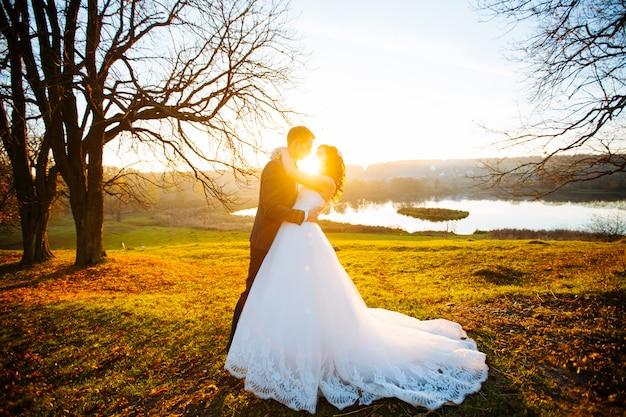 Bruiloft. mooi paar zoenen in de zon Premium Foto