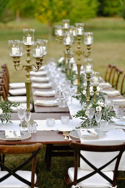 Bruiloft tabel ingericht op het gras met gasten zitplaatsen buiten in de tuinen met brandende kaarsen ingericht Gratis Foto
