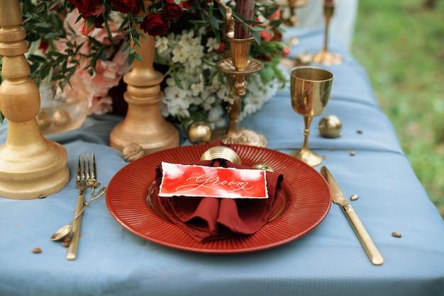 Bruiloft tafeldecoratie in gouden en rode kleuren. Premium Foto
