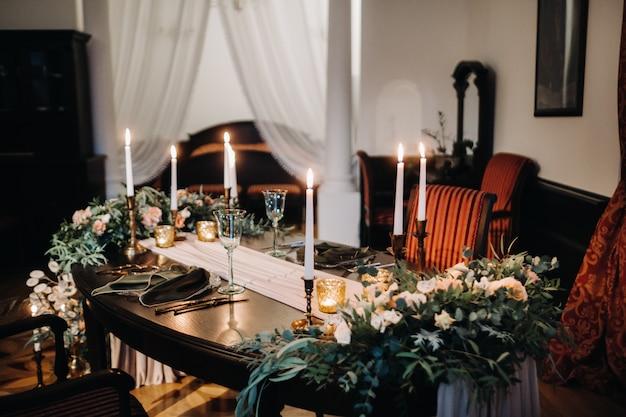 Bruiloft tafeldecoratie met bloemen op de tafel in het kasteel, tafeldecoratie voor het diner bij kaarslicht. diner met kaarsen. Premium Foto