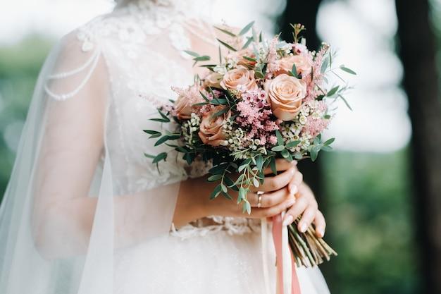 Bruiloftsboeket in de handen van de bruid Premium Foto