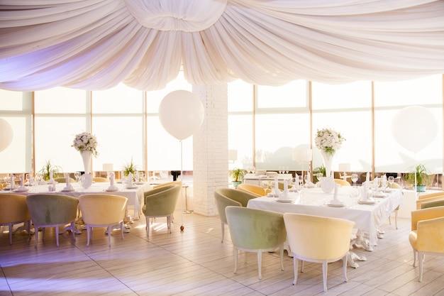 Bruiloftsdecor, bruiloftstafels in restaurant met witte bloemen en enorme witte ballonnen Premium Foto