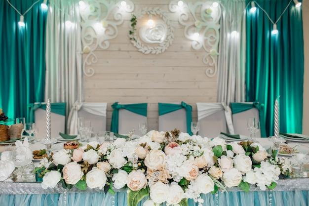 Bruiloftstafel voor bruid en bruidegom, versierd met bloemensamenstelling gemaakt van witte rozen, in aquamarijn tinten Gratis Foto