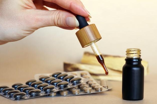 Bruin natuurlijk medicijn in een klein flesje met een pipet Gratis Foto