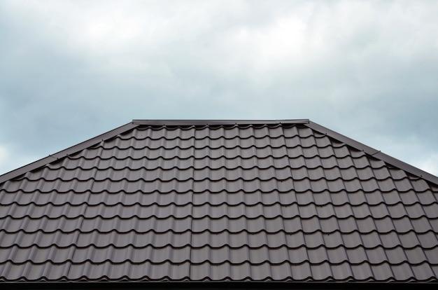 Bruine daktegels of dakspanen op huis als achtergrond. nieuw overlappend bruin klassiek dakwerkmateriaaltextuurpatroon op een echt huis Premium Foto