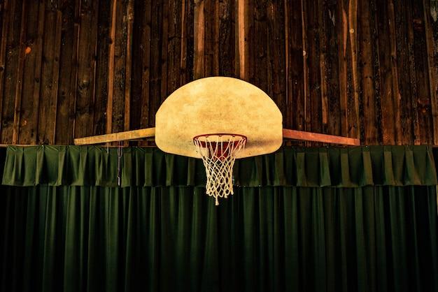 Bruine en rode basketbalring dichtbij groene gordijnen Gratis Foto