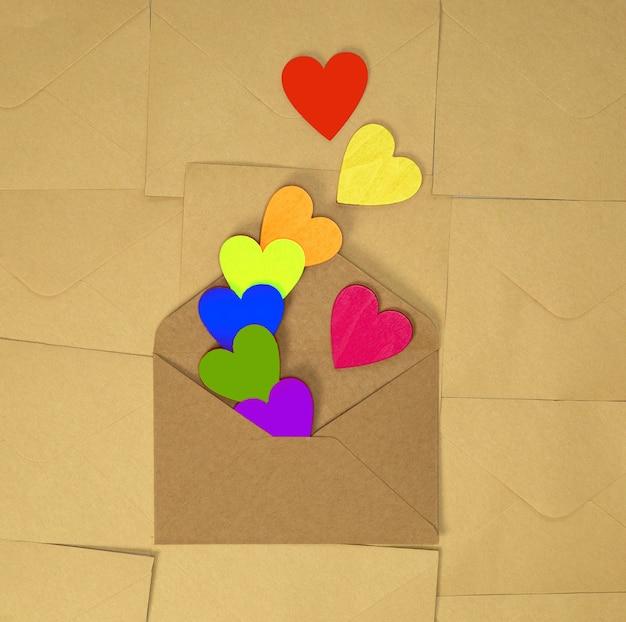 Bruine envelop van kraftpapier met verschillende regenboogkleurige harten op effen bruin Premium Foto