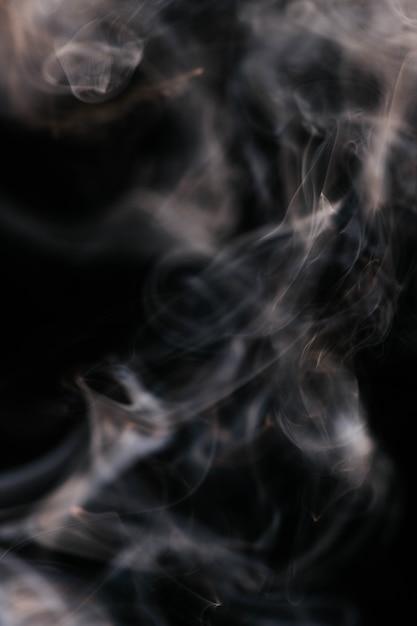 Bruine golvende rook op zwarte achtergrond Gratis Foto