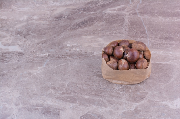 Bruine kastanjes in een papieren mand op de steen Gratis Foto