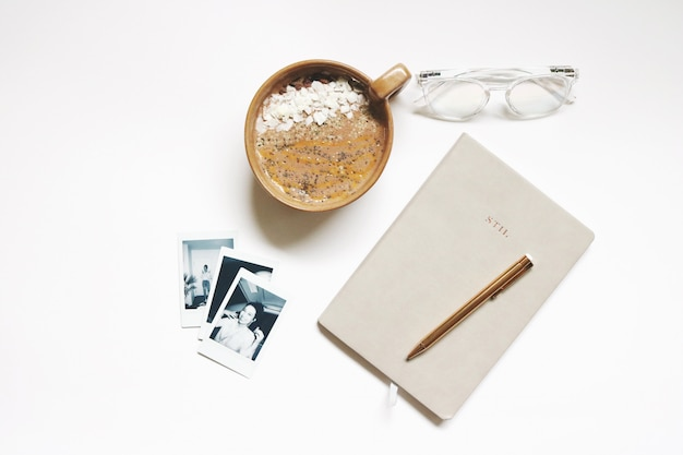 Bruine keramische beker naast notebook en pen Gratis Foto