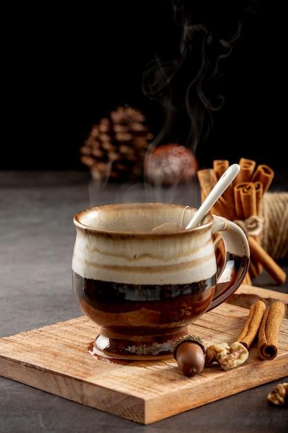 Bruine kop met thee en kaneelstokjes op een houten steun Gratis Foto