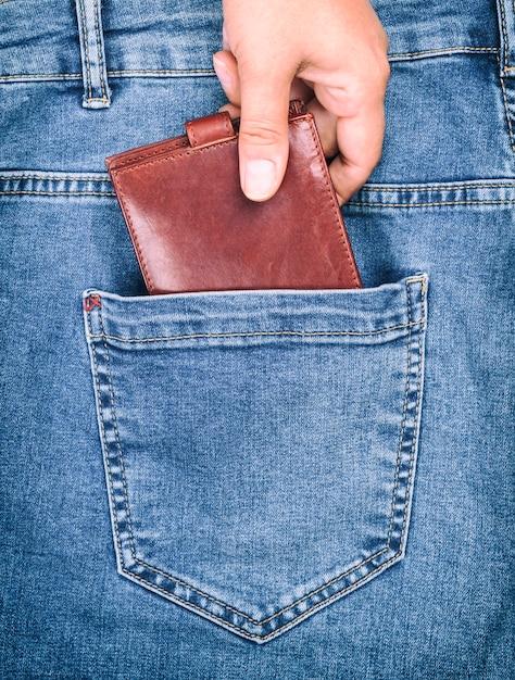 Bruine lederen tas ligt in de achterzak van een spijkerbroek Premium Foto