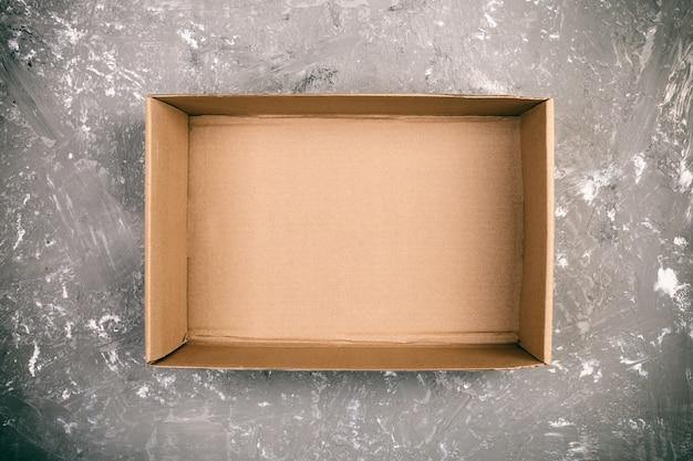 Bruine lege kartonnen doos op cement grijze oppervlak geopend Premium Foto