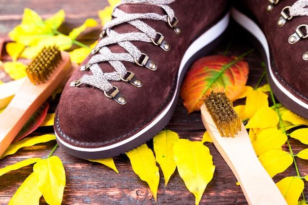 Bruine man suede laarzen op houten met bladeren. suede borstels voor schoenen. herfst- of winterschoenen. Premium Foto