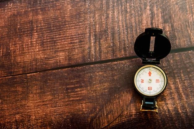 Bruine oude houten achtergrond die een reiskompas isoleert met exemplaarruimte. Premium Foto