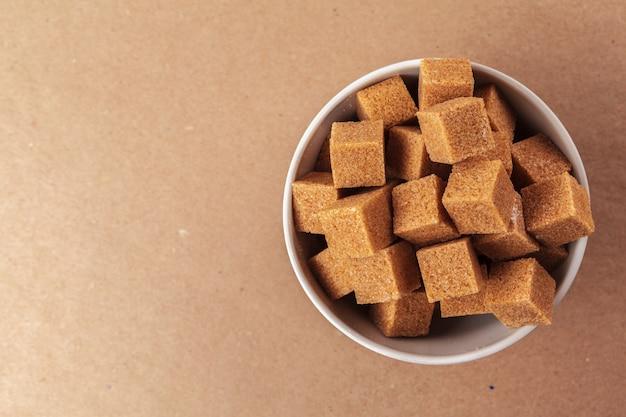 Bruine rietsuikerkubussen op een lichtbruine achtergrond Premium Foto