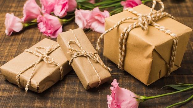 Bruine verpakte geschenkdozen en roze eustomabloemen op houten oppervlakte Gratis Foto