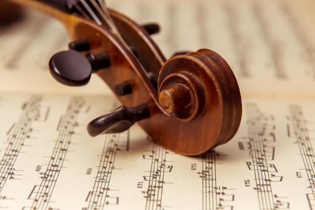 Bruine viool die op een muziekblad ligt. Premium Foto