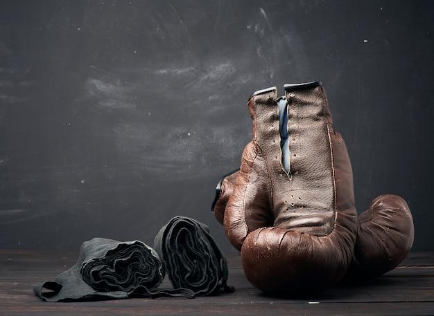 Bruinleren vintage bokshandschoenen en zwart elastisch handverband Premium Foto
