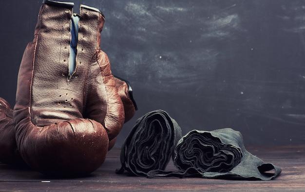 Bruinleren vintage bokshandschoenen en zwart elastisch verband voor handen op een zwarte achtergrond Premium Foto