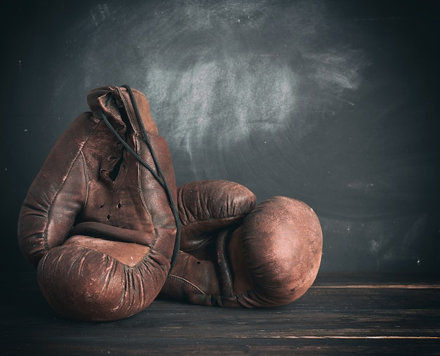 Bruinleren vintage bokshandschoenen op een zwarte achtergrond Premium Foto