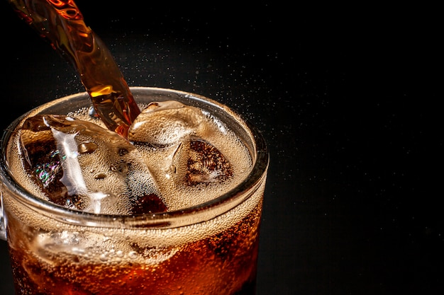 Bruisend sprankelend cola-water verfrissende bubbelende frisdrank met ijsblokjes. koude frisdrank cola koolzuurhoudende vloeistof fris en koel ijsdrank in een bril. verfrissend en doof dorstconcept. Premium Foto