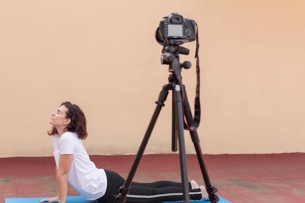 Brunette blogger die yogaroutine opneemt Gratis Foto