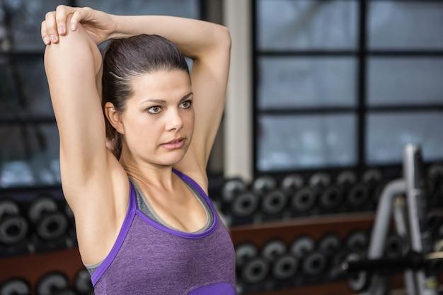 Brunette die haar wapens uitrekt bij de gymnastiek Premium Foto