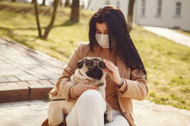 Brunette in een masker loopt met pug Gratis Foto