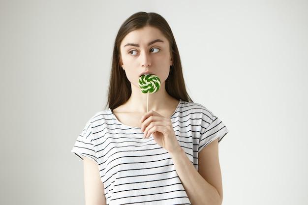 Brunette jonge vrouw op strikt dieet likken kleurrijke geelgroene lolly in het geheim, zijwaarts kijkend, bezorgd over betrapt worden op het eten van ongezonde harde suikerspin Gratis Foto