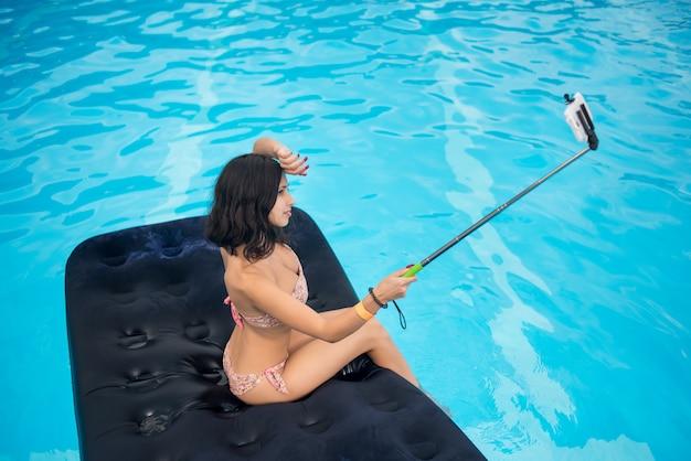 Brunette maakt selfie foto op de telefoon met selfie stok op matras in zwembad Premium Foto