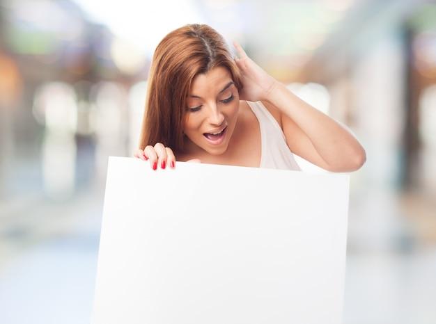 Brunette meisje met een verbaasd gezicht die lege raad Gratis Foto